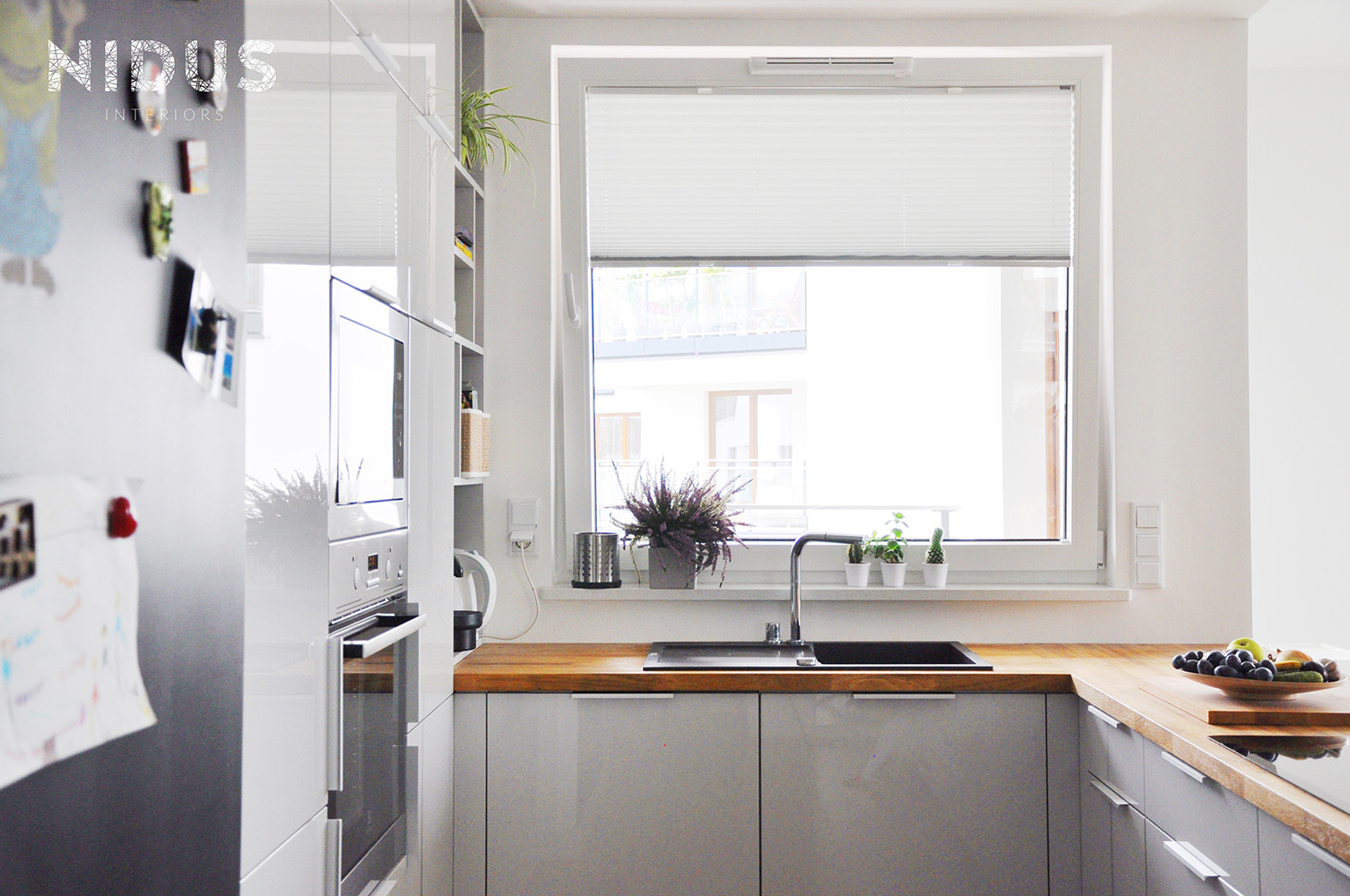Kuchnia z szarymi frontami i drewnianym blatem otwarta na salon