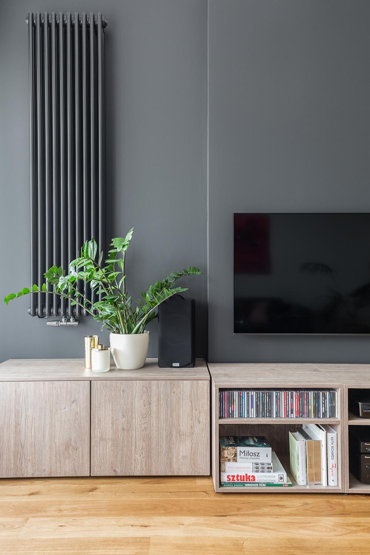 Czarna ściana telewizyjna z dekoracyjnym grzejnikiem